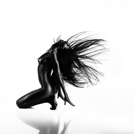 artistic nude: artistic nude of a young woman with black painted skin isolated on white background, sitting on her knees, throwing her hair back Stock Photo