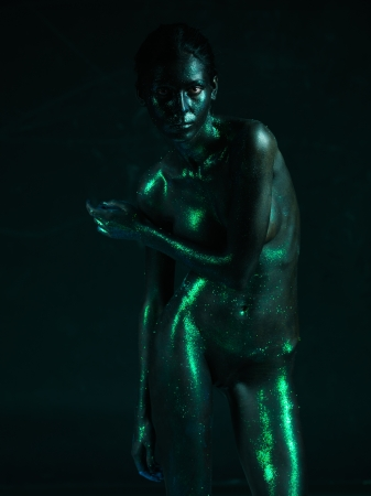 female nudity: artistic low-key nude of a young woman with glittery blue skin, posing and looking at the camera Stock Photo