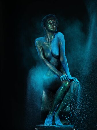 naked statue: artistic low-key nude of a young woman sitting on a chair. her skin is shiny and she has a cloud of blue dust around her body Stock Photo