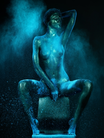 female nudity: artistic low-key nude of a young woman sitting on a chair. her skin is shiny and she has a cloud of blue dust around her body Stock Photo