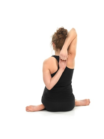 introversion: attractive young woman in advanced sitting yoga pose, back view, on white background Stock Photo