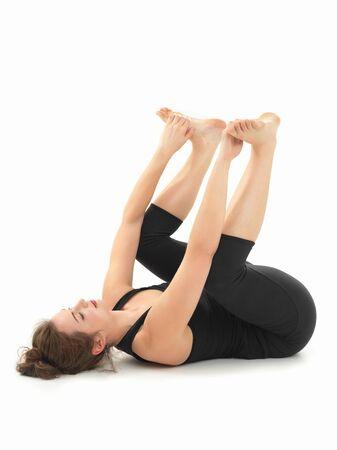 elasticidad: mujer joven que practica yoga postura de relajación, vista lateral completo, vestida de negro, sobre fondo blanco