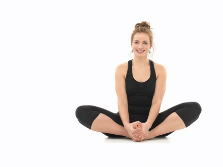 young girl smiling, demonstrating yoga pose, full front view, dressed in black, on white background Stock Photo