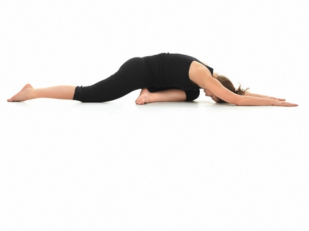 introversion: young girl in yoga pose, side view, dressed in black, on white background Stock Photo