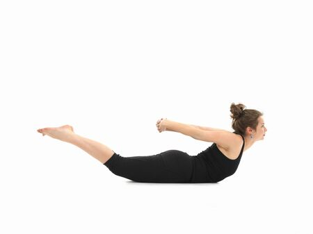 side pose: young caucasian woman in lying yoga pose, side view, full body, dressed in black, on white background