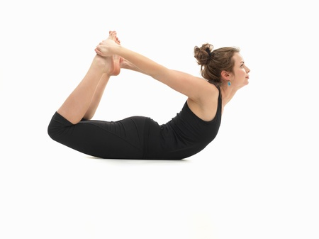 introversion: young attractive woman on the floor, in reversed yoga pose, side view, dressed in black on white background