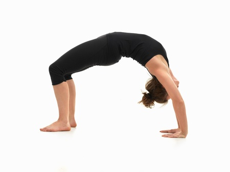 caucasian woman on the floor, in reversed yoga pose, side view, dressed in black on white background photo