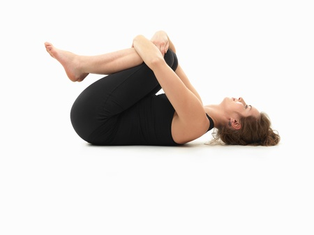 introversion: caucasian woman on the floor, in relaxed yoga pose, side view, dressed in black on white background