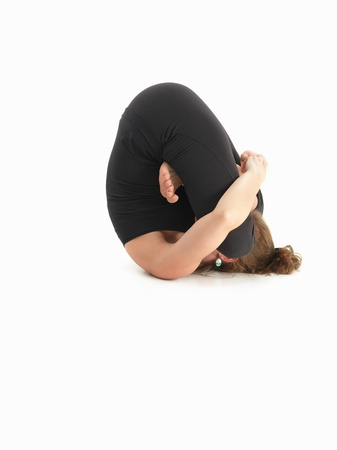 introversion: young woman in yoga pose, face invisible, body side view, dressed in black, on white background