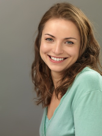 one of a kind: studio portrait of beautiful, young woman, smiling, on gray background Stock Photo