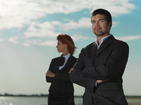 side job: confindent young businesswoman and businessman, on a desert beach, looking at the camera Stock Photo