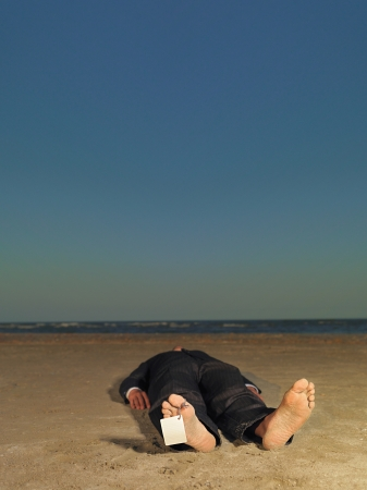 conceptual portrait of dead businessman, stranded on a desert beach, with a blank label attached to his toe photo