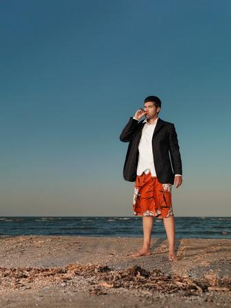 cigar smoke: confident, young businessman in shorts, smoking a cigar on the sea shore