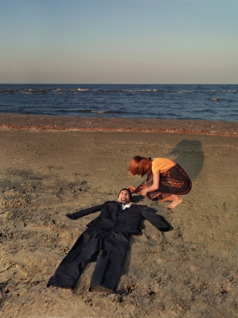 bury: exhausted young businessman stranded on sea shore, with an empty suit where his body should be, and a young woman comforting him