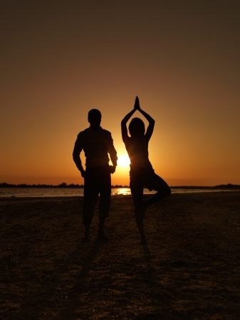 yoga sunset: young businessman and businesswoman on the sea shore, standing in a yoga position, meditating at sunset