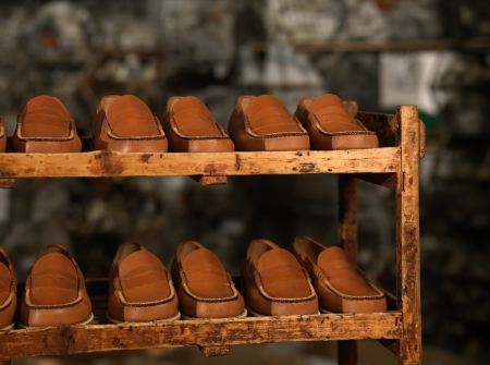 moccasins: detail of a storage zone in a shoe factory, with brown moccasins aligned on wooden shelves