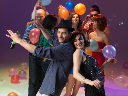 young couple dancing back to back, with friends, ballons and bubbles on background photo