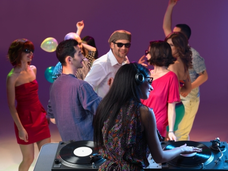 female dj mixing at party, back view, with peple dancing in front of her photo