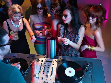 energy drinks: young women holding drinks and talking to the dj at a party Stock Photo