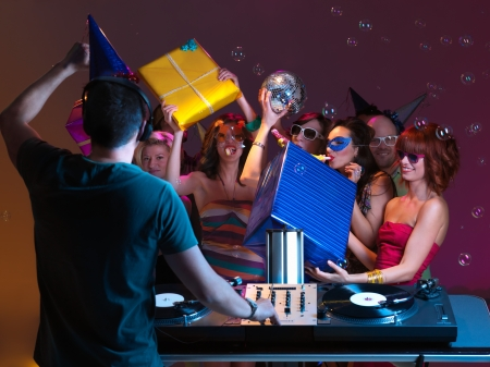 girls receiving presents and playing with them, at a party, with dj mixing music photo