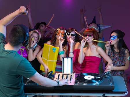 s horn: group of girls playing with party horns and dancing, with dj mixing music Stock Photo