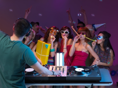energy mix: girls amusing themselves at party, dancing and playing, in front of dj mixing music, with poeple danging in the background Stock Photo
