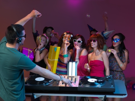 dj headphones: young women dancing at party and playing with party horns, with dj mixing and dancing and people dancing in the background Stock Photo