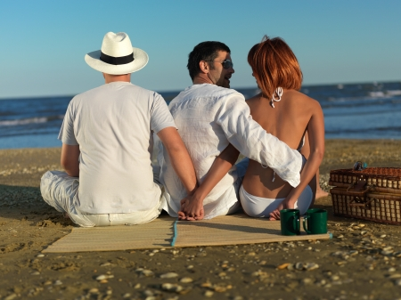 cheating: young woman talking with the boyfriend, while holding hands with another man, at a picnic by the sea shore