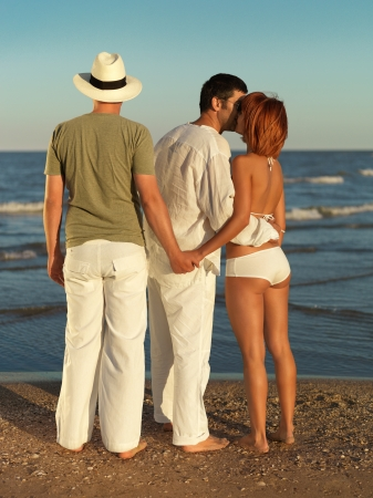 young woman kissing one man and holding hands with another, by the sea shore photo