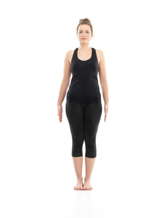 introversion: young attractive woman in beggiging yoga posture, dreesed in blak, on white background