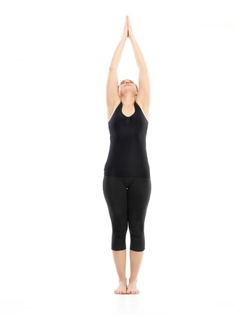 introversion: preparation for yoga posture, demonstrated by young woman, dressed in black, on white background Stock Photo