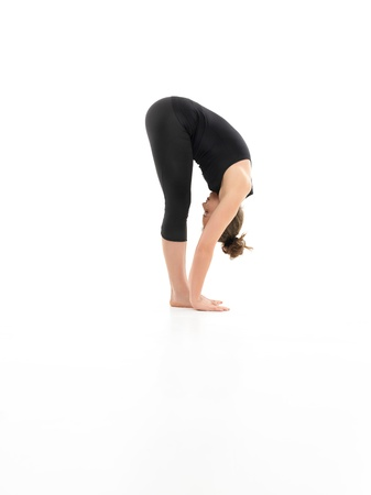 introversion: forward bending yoga pose, shown by younf female, dreesed in balck, on white background, side view