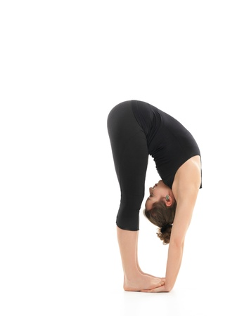 introversion: young girl in difficult forward bending yoga posture, dressed in black, on white background
