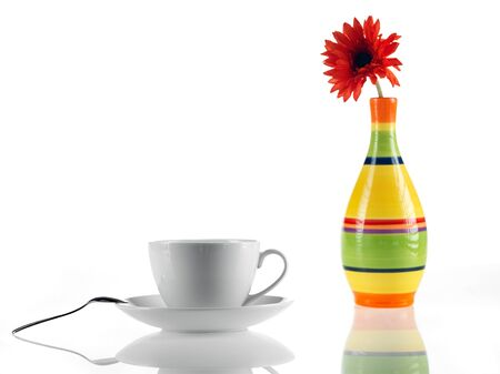 tea cup and spoon and vase with daisy photo