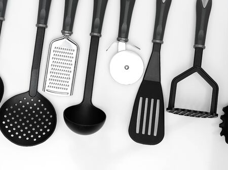 implements: kitchen utensils hanging white background