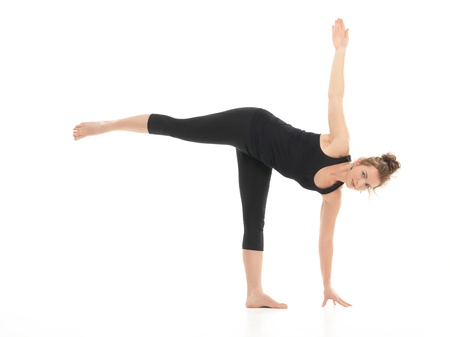 chandrasana: yoga posture demonstration by young blonde woman, dressed in black on white background Stock Photo