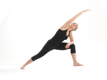 full body view of young slim woman in yoga posture, dressed in black on white bacground photo