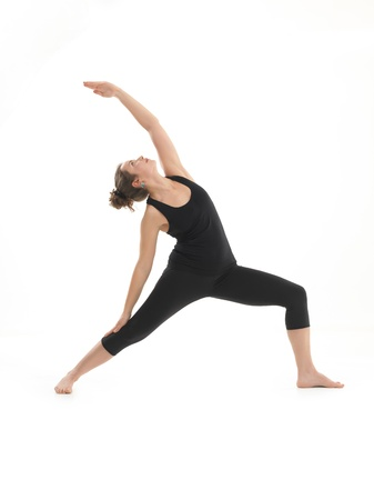 front view of young blonde woman in balanced yoga pose, dressed in black on white background photo