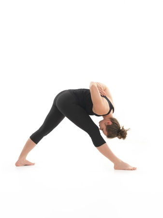 introversion: young, blonde woman practicing yoga posture, with face obscured, ressed in black, on white blackground Stock Photo