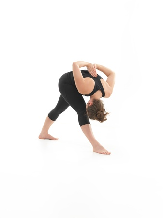 introversion: young blonde woman dmonstrationg yoga pose, bent fowrad, with face obscured, dressed in blak, on white background