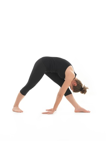 side view of young woman in yoga posture, face obscuredm dressed in blak, on white backgrond photo