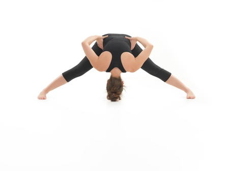 blak white: frontal view of stretching yoga posture, by young woman, dressed in blak on white background