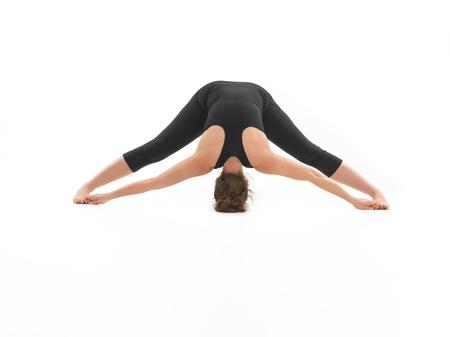 paz interior: mujer joven de pie en postura de yoga, vestida de negro, sobre fondo blanco Foto de archivo