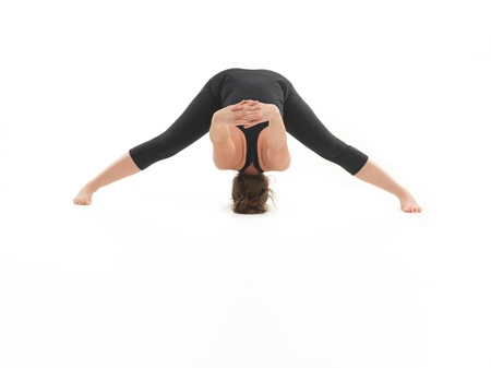 introversion: frontal view of difficult yoga pose demonstrated by young blonde female, dressed in black, on white background
