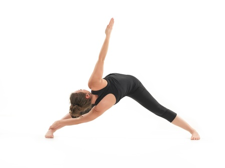 hatha: young, blonde woman demonstrating stretching yoga postrure, with face obscured, dressed in blak, on white background