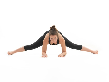 introversion: frontal view of young woman demonstrating difficult yoga pose, dressed in black, on white background