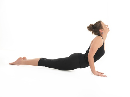 COBRA: young woman showing back bent yoga posture, side view, dressed in black on white background