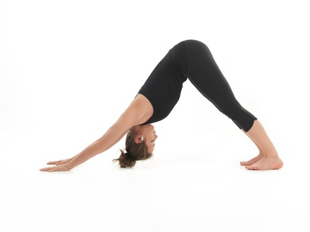 hatha: young woman sitting in stretching yoga pose, dressed in black, on white background