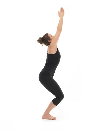 introversion: full body view of young woman demonstrating yoga pose, dressed in black, on white background