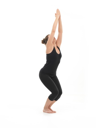 introversion: semi-profile of young woman in yoga posture, dressed in blac, on white background